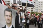 Syrian people hold posters of President Bashar al-Assad outside the foreign ministry in Damascus