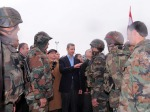 Syria's President Bashar al-Assad speaks to soldiers during a tour in the Baba Amr neighbourhood of Homs