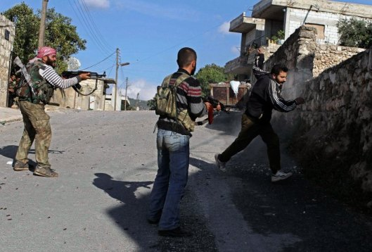 Free Syrian Army members fire on a man they suspect to be from the pro-government forces during a combing operation in Harem town