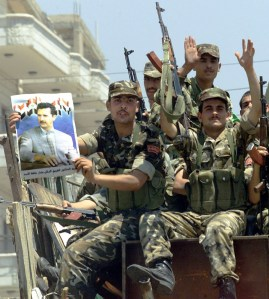 237633-a-syrian-soldier-displays-a-poster-of-president-bashar-al-assad-as-he