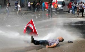 Man is hit by a jet of water as riot police use a water cannon to disperse demonstrators during a protest against Turkey's PM Erdogan and his ruling AKP in central Ankara