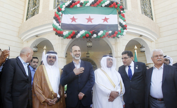 Syrian National Coalition leader Moaz Alkhatib attends the opening of its embassy in Doha