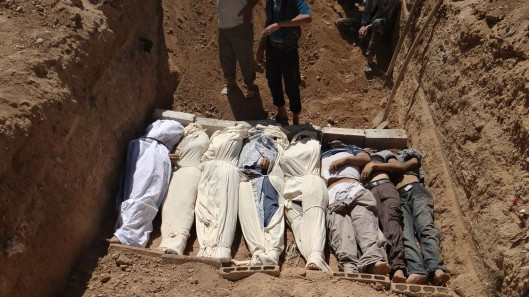 bodies being buried in a suburb of Damascus