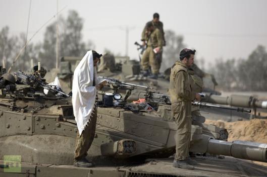 israeli-soldiers-praying-beside-army-deployment