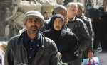 Residents wait to receive food aid distributed by UNRWA at the besieged al-Yarmouk camp