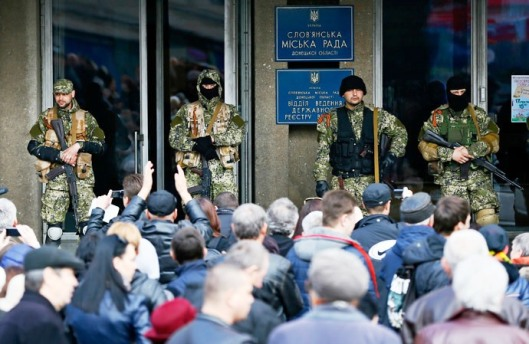 Anti-government armed men stand guard as pro-Russian supporters gather outside office in Slavians