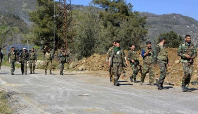 Syrian soldiers saunter down a road close to Kasab as though they know each square foot like the backs of their hands