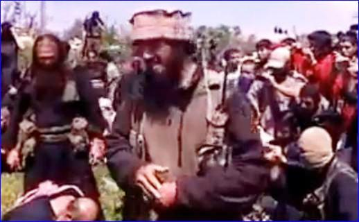 In this undated image taken from a video posted in 2013, a man whom Turkish intelligence identified as Magomed Abdurrahmanov, foreground, is seen speaking to a crowd moments before he decapitates one of three men identified as Christians (image from Live Leaks video).