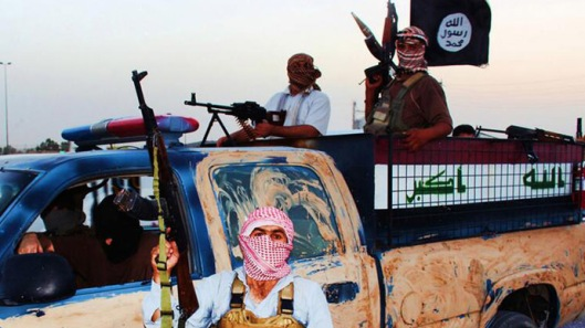 Militants of the Islamic State of Iraq and the Levant (ISIL) riding in a captured vehicle left behind by Iraqi security forces at an unknown location in the Salaheddin province. (AFP Photo)