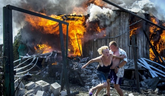 Local residents escape from a fire in the house that came under Ukrainian forces' air attack on the village of Luganskaya on July 2, 2014 (RIA Novosti/Valery Melnikov)