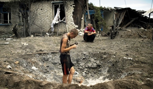 Locals are sitting outside a house destroyed in the Ukrainian armed forces' air attack on the village of Luganskaya on July 2, 2014 (RIA Novosti/Valeriy Melnikov)