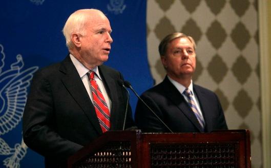 U.S. Senator John McCain speaks as compatriot Senator Lindsey Graham looks on during a news conference in Cairo