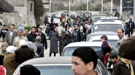 Image: A handout picture released by SANA on January 25, 2014 shows families returning to their houses in the Barzeh neighborhood of Damascus after the authorities in the area repaired the infrastructures.