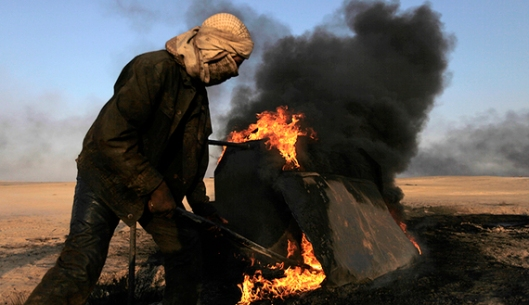 A man works at a makeshift oil refinery site in al-Mansoura village in Raqqa