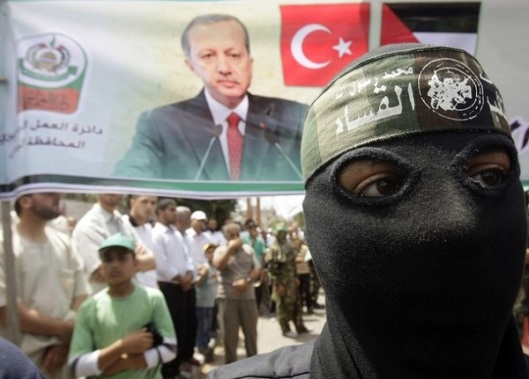 A masked member of Hamas stands in front of a banner during a protest in Central Gaza Strip