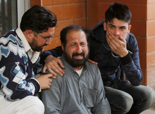 Relatives of a student, who was injured during an attack by Taliban gunmen on the Army Public School, outside Lady Reading Hospital in Peshawar