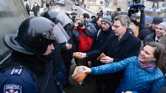 US Assistant Secretary of State for European and Eurasian Affairs Victoria Nuland (R) and US Ambassador Geoffrey Pyatt (2nd R) distribute bread to riot police near Independence square in Kiev December 11, 2013.(Reuters / Andrew Kravchenko)
