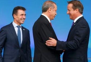 Britain's Prime Minister David Cameron and NATO Secretary-General Anders Fogh Rasmussen greet Turkey's President Recep Tayyip Erdogan at the start of the NATO summit at the Celtic Manor resort, near Newport