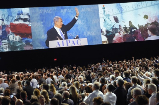 Israel's PM Netanyahu is shown on a video screen as he waves at the end of his remarks to the AIPAC policy conference in Washington
