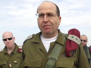 File photo of Israel's armed forces chief Moshe Yaalon walking after a visit to the Kissufim crossing in Gaza strip