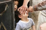 An activist health worker administers a polio vaccination to a child in Aleppo on May 4. (Hosam Katan/Reuters)