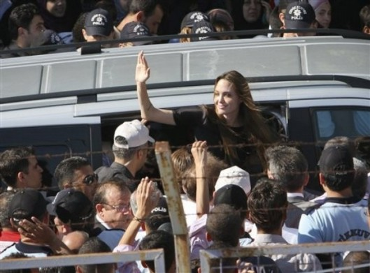 Angelina Jolie, the Hollywood celebrity and goodwill ambassador for the U.N. High Commissioner for Refugees waves as she exits a van surrounded by Syrian refugees  at the Altinozu refugee camp  near the Syrian border, Friday, June 17, 2011. (AP Photo/Selcan Hacaoglu)