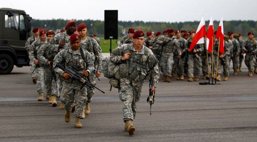 Soldiers from the first company-sized contingent of about 150 U.S. paratroopers from the U.S. Army's 173rd Infantry Brigade Combat Team based in Italy walk after unpacking as they arrive to participate in training exercises with the Polish army in Swidwin, northern west Poland April 23, 2014. The United States is sending about 600 soldiers to Poland and the three Baltic states for infantry exercises, the Pentagon said, one of its highest-profile steps yet to reassure NATO allies after Russia's seizure of Crimea. REUTERS/Kacper Pempel (POLAND - Tags: MILITARY POLITICS) - RTR3MCT1