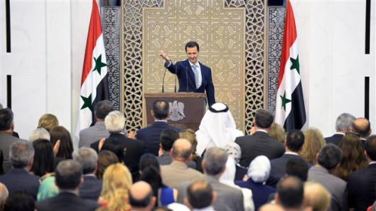 A handout picture released on July 26, 2015 by the official Syrian Arab News Agency (SANA) shows President Bashar al-Assad waving to the crowd following a speech in the capital Damascus. (AFP Photo)