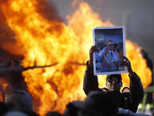A man holds up a poster of Libya's leader Muammar Gaddafi, one of several distributed among a crowd gathered to view a burning fuel truck, in Tripoli March 2, 2011. Authorities said the incident was a road traffic accident. The posters were distributed when members of the media turned up at the scene. REUTERS/Chris Helgren (LIBYA - Tags: CIVIL UNREST DISASTER POLITICS)