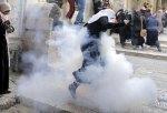 Palestinian women run away as Israeli police throw a stun grenade in Jerusalem's Old City
