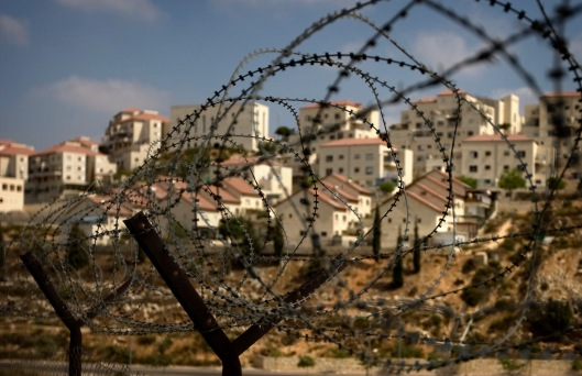 The West Bank Jewish settlement of Beitar Ilit is seen through a barbed wire fence, Friday, Sept. 4, 2009. Prime Minister Benjamin Netanyahu is expected to approve some hundreds of new housing units in West Bank settlements before slowing settlement construction, two of his aides said Friday, in an apparent snub of Washington's public demand for a total settlement freeze. (AP Photo/Sebastian Scheiner)