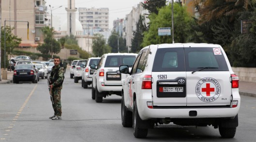 A convoy carrying Peter Maurer, president of the International Committee of the Red Cross (ICRC), drives past a member of forces loyal to Syria's President Bashar al-Assad securing the road in the Damascus suburb of Barzeh November 14, 2014. Maurer said he helped distribute aid which arrived in Barzeh on Friday, adding that he was determined to negotiate further access to other areas which have not yet received aid. REUTERS/Omar Sanadiki (SYRIA - Tags: CIVIL UNREST POLITICS CONFLICT SOCIETY) - RTR4E4WS