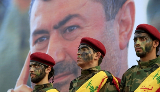 Lebanon's Hezbollah members stand at attention in front of a picture of Hassan al-Haj, one of Hezbollah's top commanders who was killed fighting alongside Syrian army forces in Idlib province, during his funeral in his hometown of al-Luwaizeh, southern Lebanon October 12, 2015. Lebanon's Hezbollah on Monday buried a commander described as the group's most important military figure to be killed in the four-year-long Syrian war. Hassan al-Haj was killed in Idlib province in northwestern Syria, where the Iranian-backed group is fighting Syrian rebels in an offensive in support of President Bashar al-Assad and backed by Russian air strikes. REUTERS/Ali Hashisho - RTS450Y