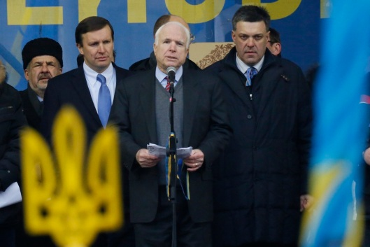 U.S. Senator John McCain, center, speaks as Democratic senator from the state of Connecticut, Chris Murphy, second left, and Opposition leader Oleh Tyahnybok, right, stand around him during a Pro-European Union rally in Independence Square in Kiev, Ukraine, Sunday, Dec. 15, 2013. Ukrainian national symbol is in the foreground. About 200,000 anti-government demonstrators converged on the central square of Ukraine's capital Sunday, a dramatic demonstration that the opposition's morale remains strong after nearly four weeks of daily protests. (AP Photo/Dmitry Lovetsky)